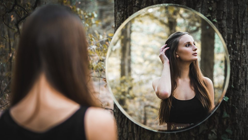What is your identity? Woman looking in mirror.