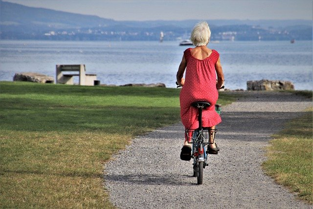 older fit woman riding a bicycle with ocean in the background